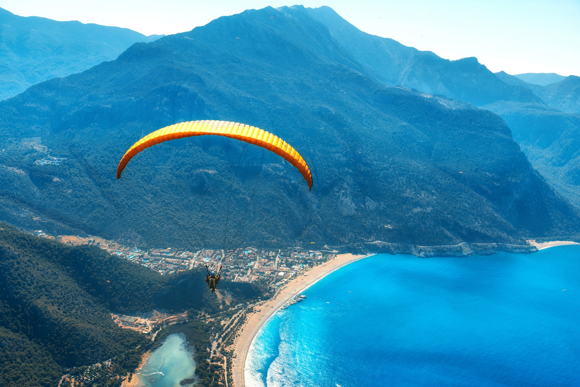 Paraglider tandem flying over the sea with blue water and mountains